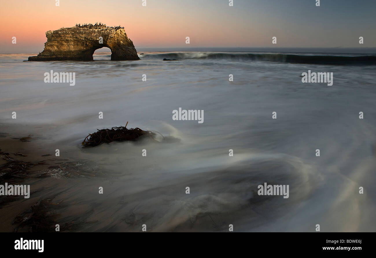 An arch stands against a twilight sky at Natural Bridges State Park, Santa Cruz, California, USA. - Stock Image