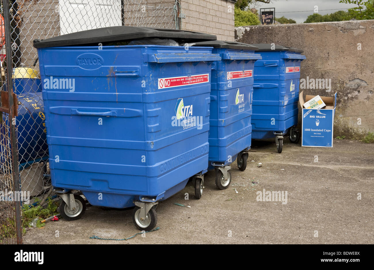 Industrial Garbage Containers : Three large blue plastic commercial wheelie bins full of