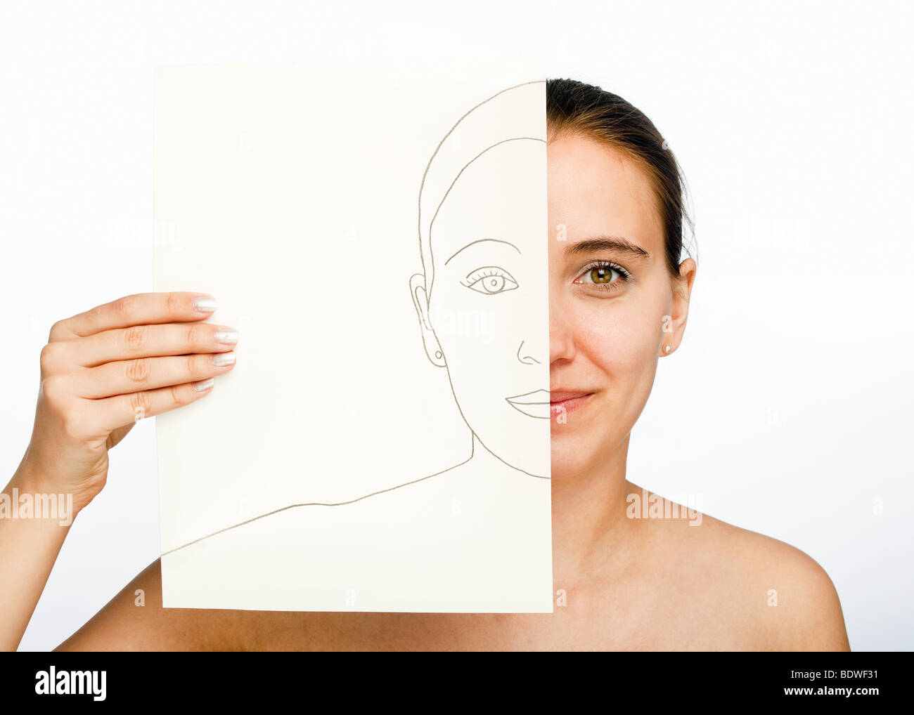 Young woman holding a drawn portrait of herself - Stock Image