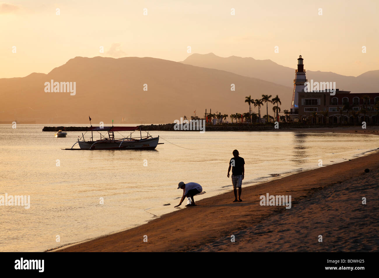 People walking on the beach in the evening, lighthouse, boat, banka, palm trees, romantic mood, Olongapo City, Subic - Stock Image