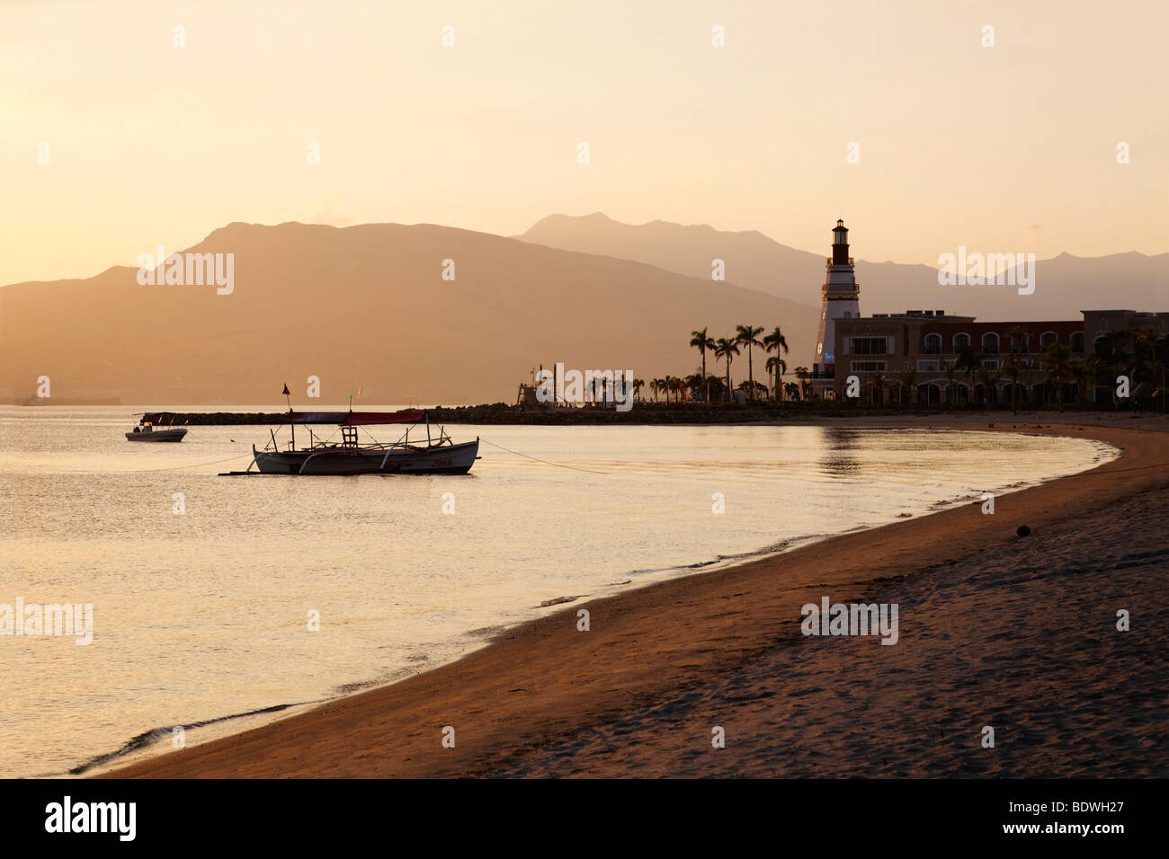 Beach in the evening, fishing boat, banka, lighthouse, mountains, palm trees, romantic mood, Olongapo City, Subic - Stock Image