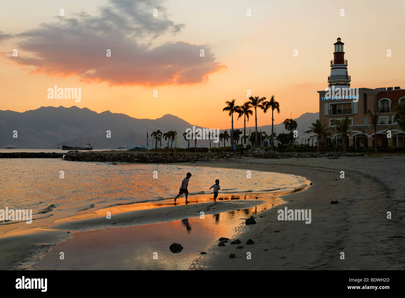 Children playing on the beach in the evening, lighthouse, boat, banka, palm trees, romantic mood, Olongapo City, - Stock Image