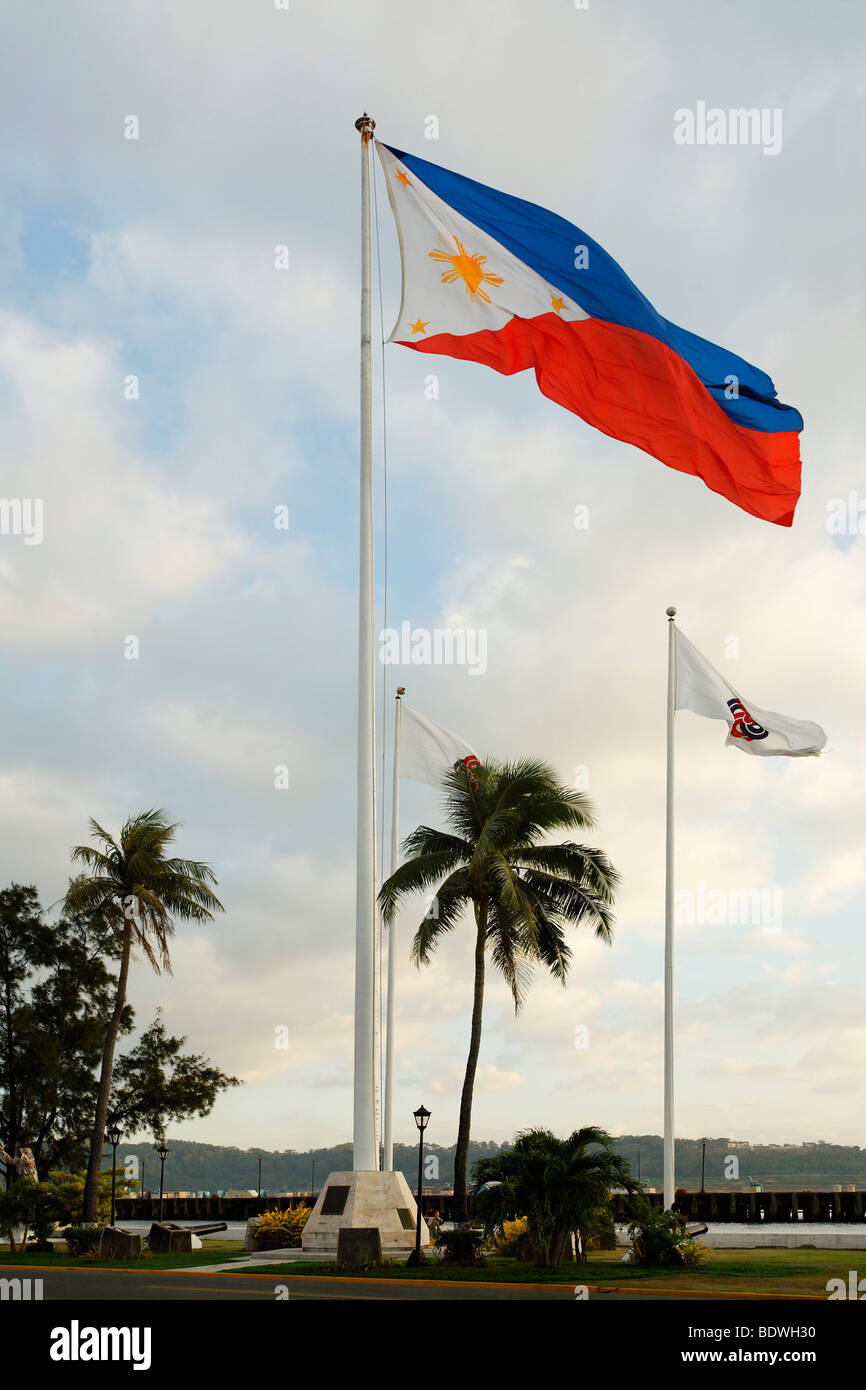Philippine national flag, mast, palm trees, natural harbour, freeport, port, Olongapo City, Subic Bay, Luzon island, - Stock Image