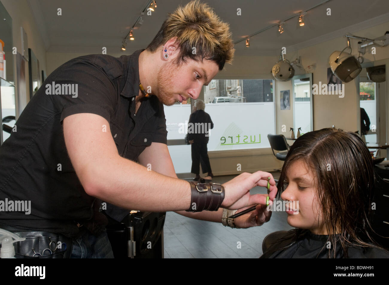 A teenager getting her hair cut by a hairdresser in a hairdressing salon - Stock Image