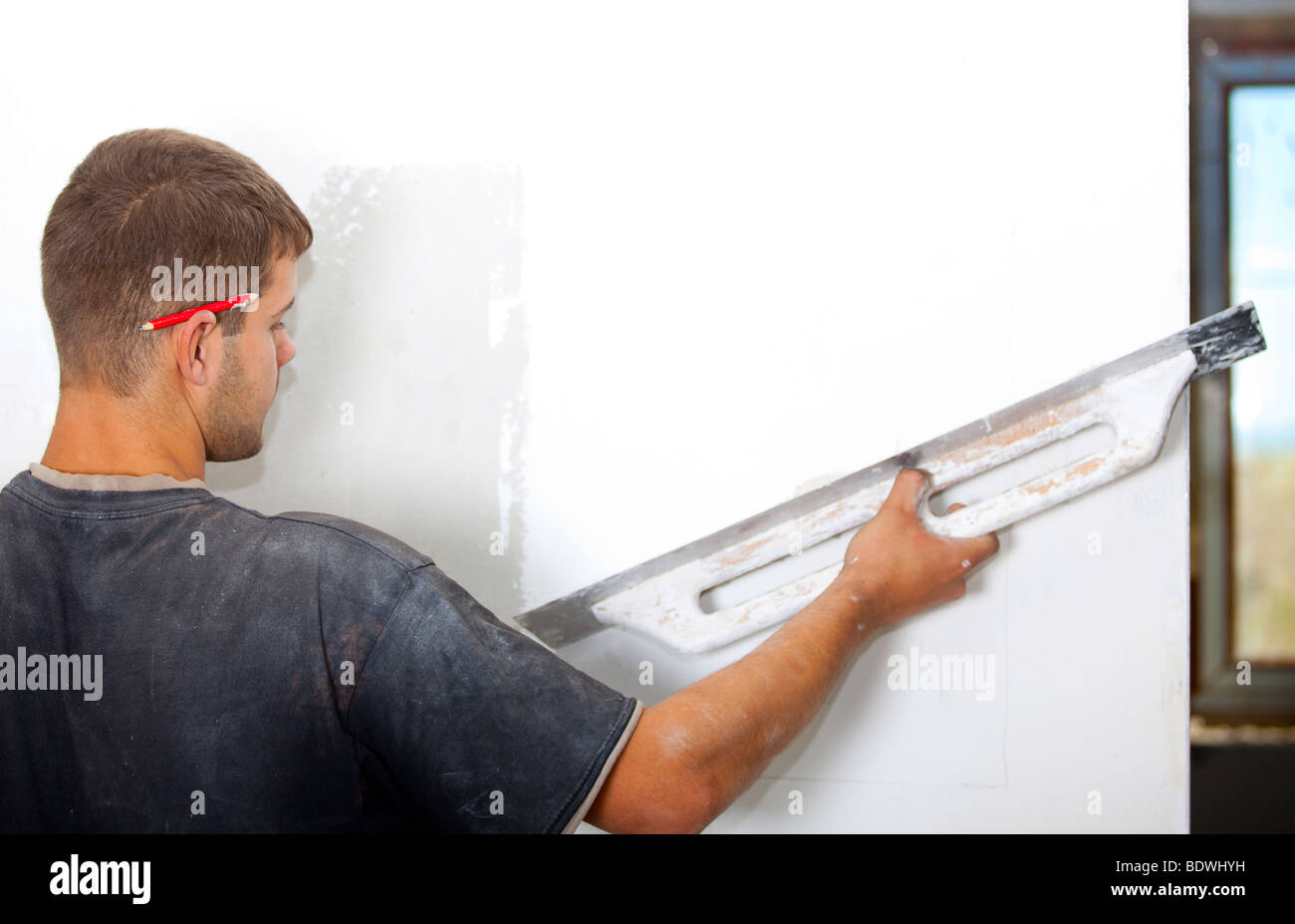 Man plastering the wall with a large spatula. At the corrosion imposed gypsum. Sharpness to face. Horizontal Directional Stock Photo
