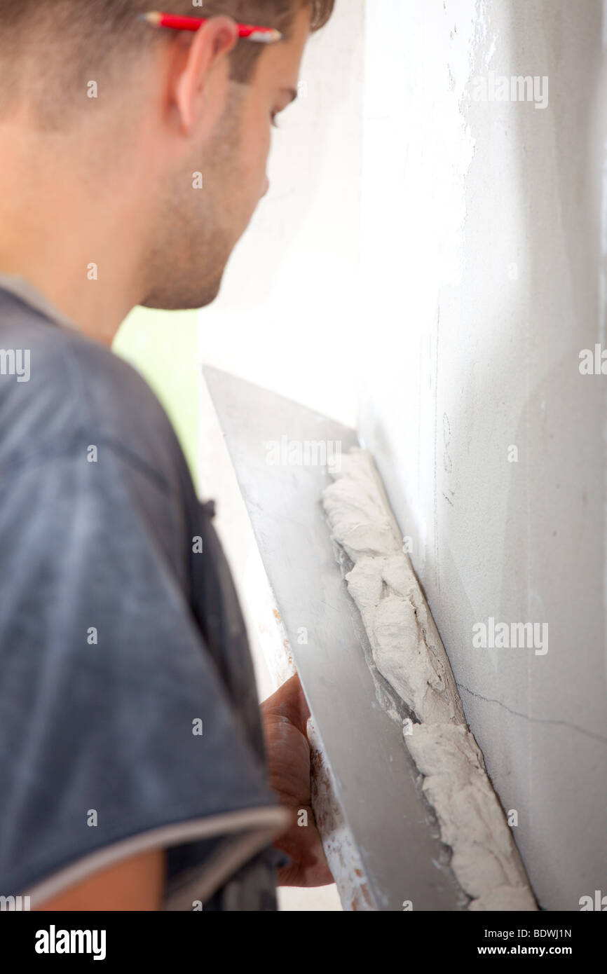 Man plastering the wall with a large spatula. At the corrosion imposed gypsum. Sharpness to spatula. Vertical Directional Stock Photo