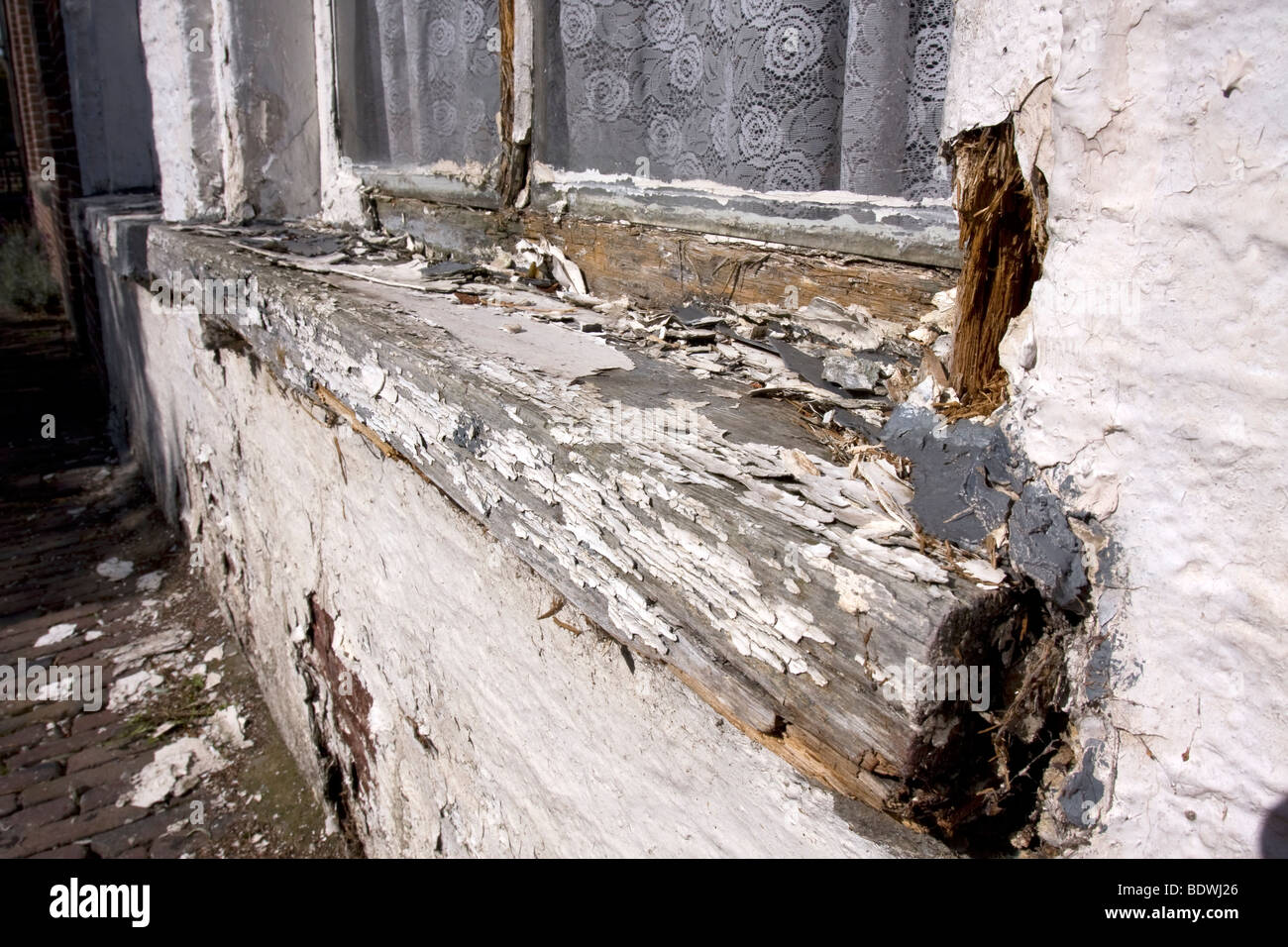 White paint peeling of an old, badly maintained, wooden windows frame. Stock Photo