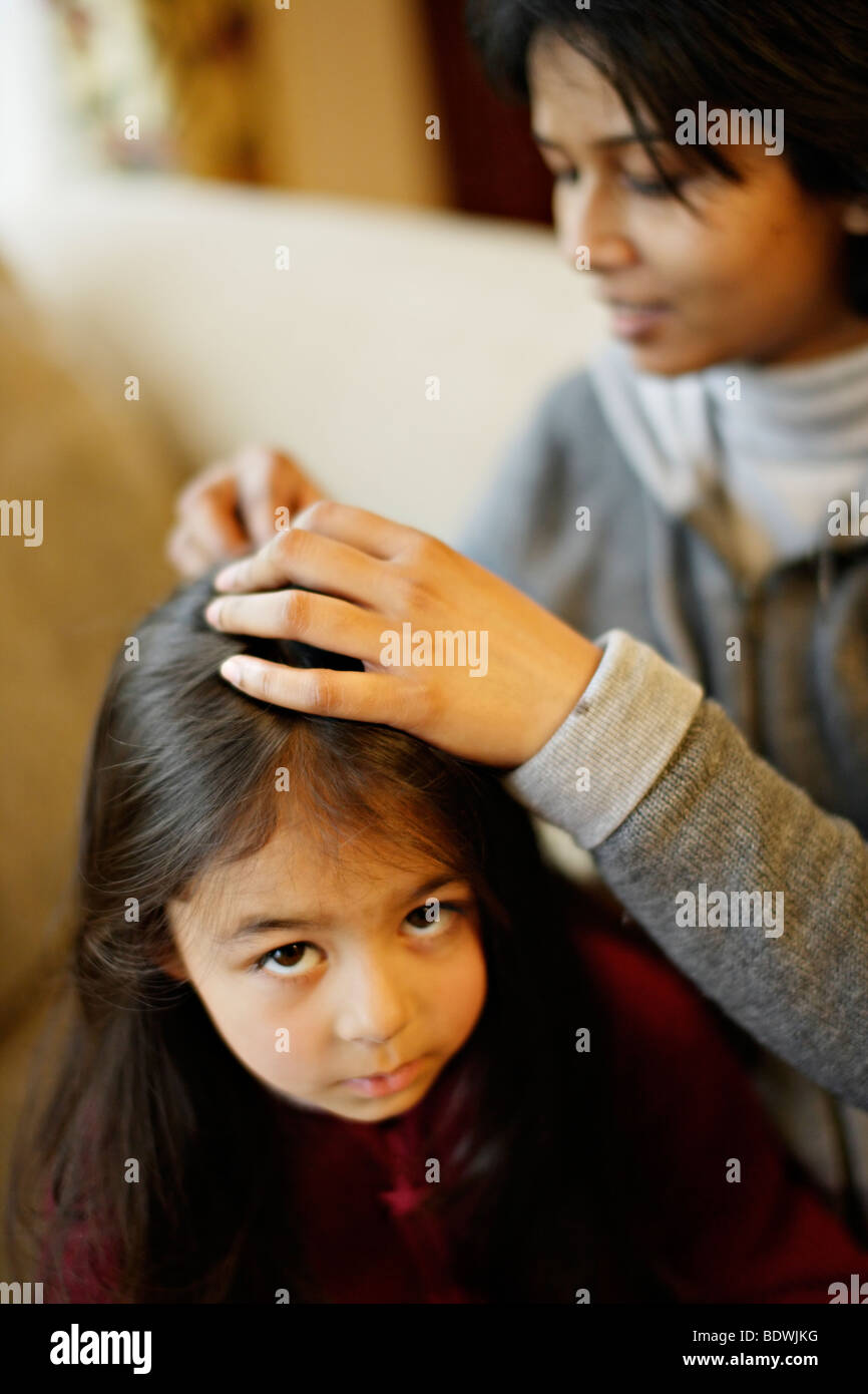 Mother picks nits from daughter's hair - Stock Image
