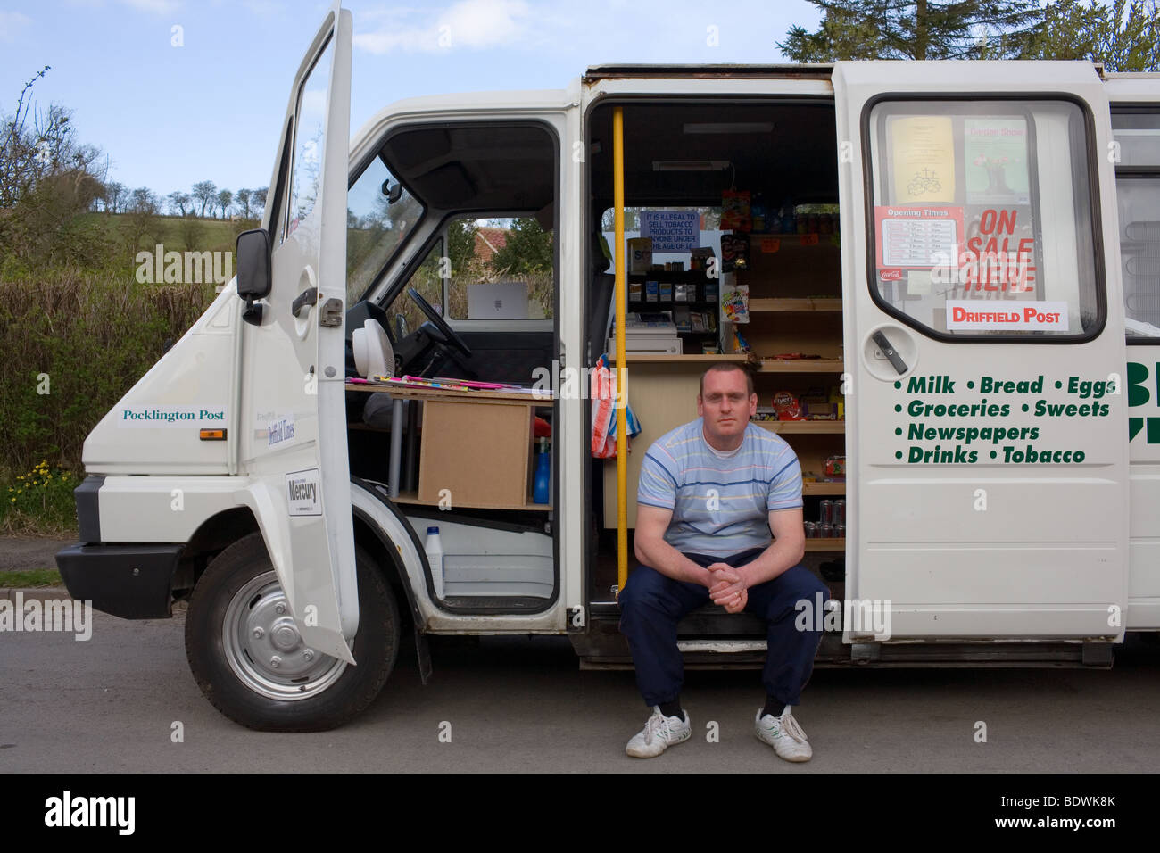 A man sits in his mobile shop business that he started after being made redundant. - Stock Image