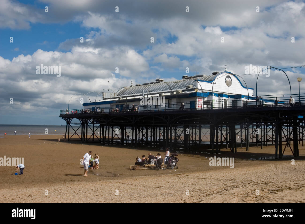 People on the beach near Cleethorpes Pier at low tide - Stock Image