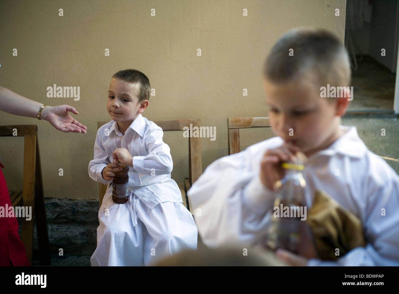 Boys backstage in traditional costume drink soda from bottles during a folk event in Pecs, Hungary. - Stock Image