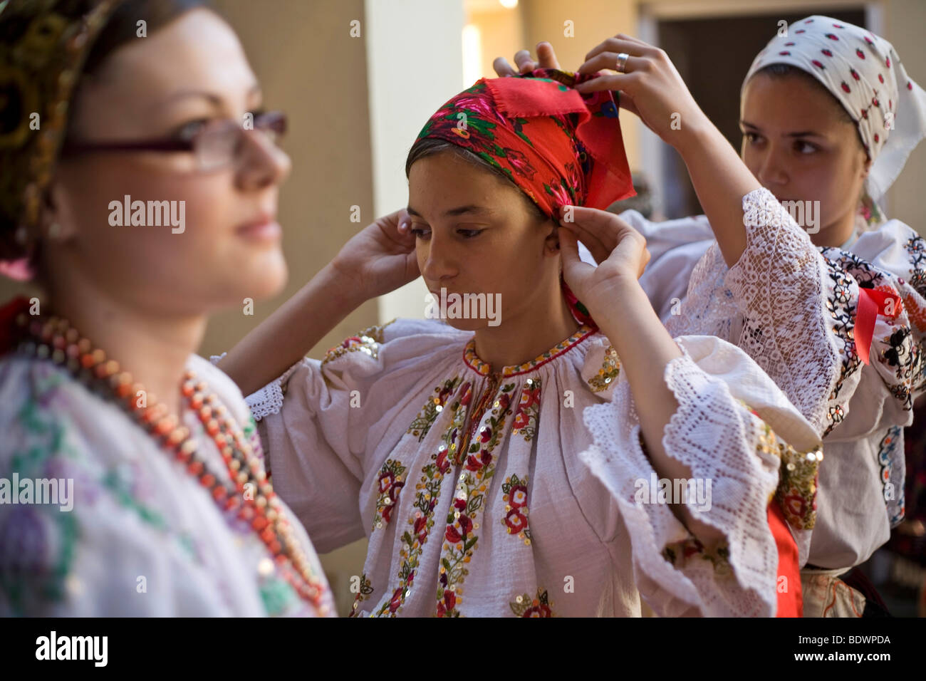 Girls help each other to tie a costume backstage during a folk event in Pecs, Hungary - Stock Image