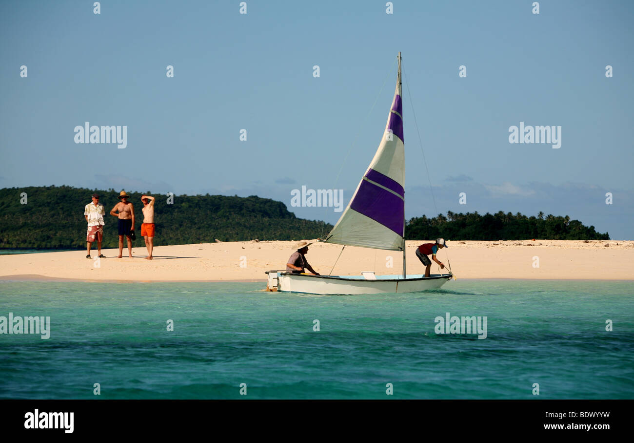 A father and son sail a small yacht in the Vavau archipelago Tonga - Stock Image