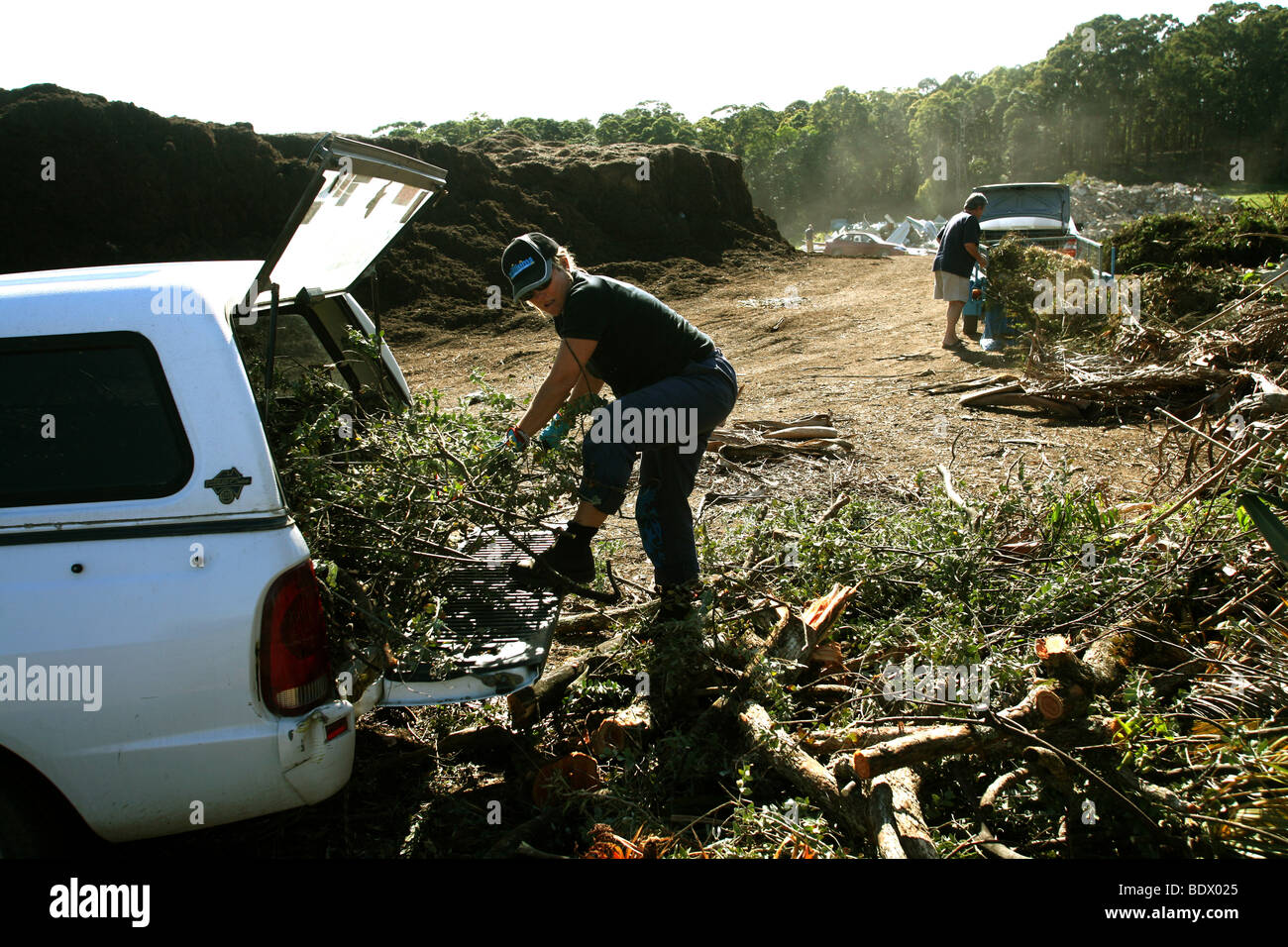 A woman recycles green waste from the garden at a rubbish dump where it is converted to mulch. - Stock Image