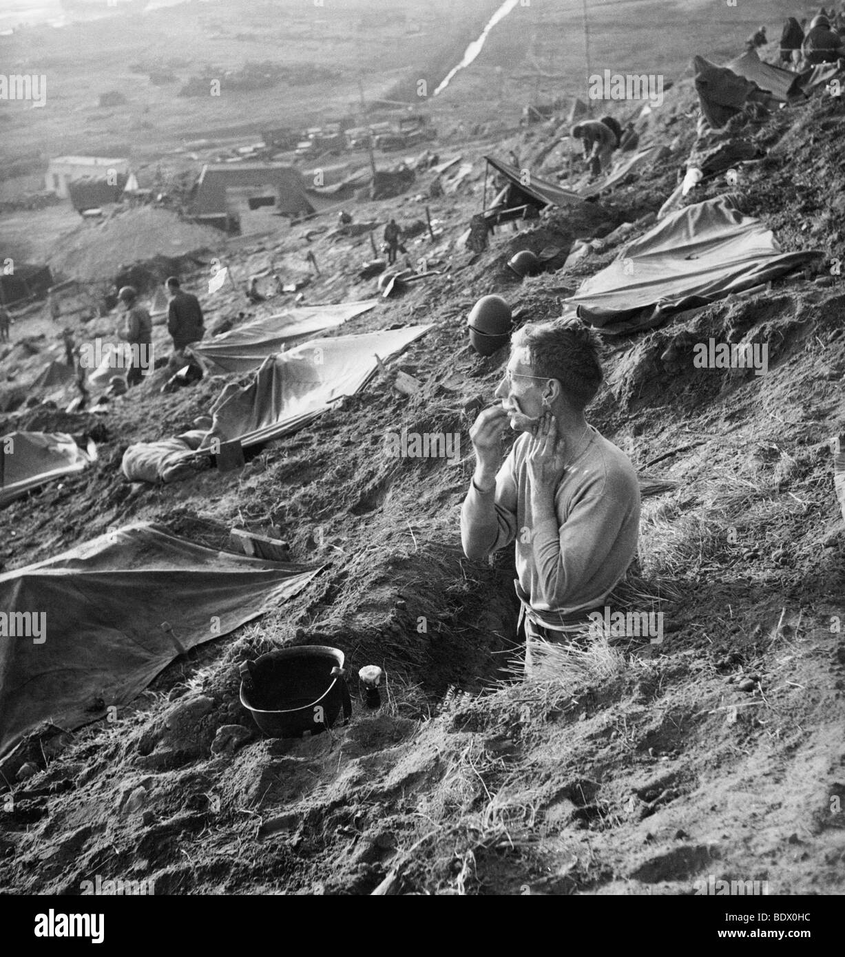D-DAY LANDINGS 1944 - US soldier shaves in his foxhole near Cherbourg in June 1944 Stock Photo