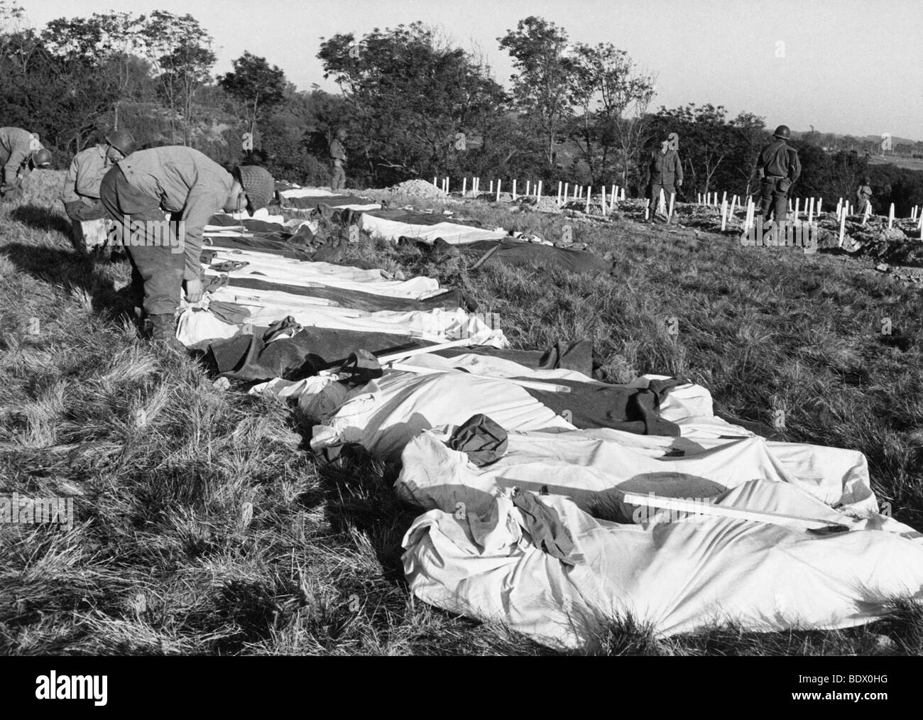 D-DAY CASUALTIES - American dead in body bags await temporary burial on 8 June 1944, a white stake carries their - Stock Image