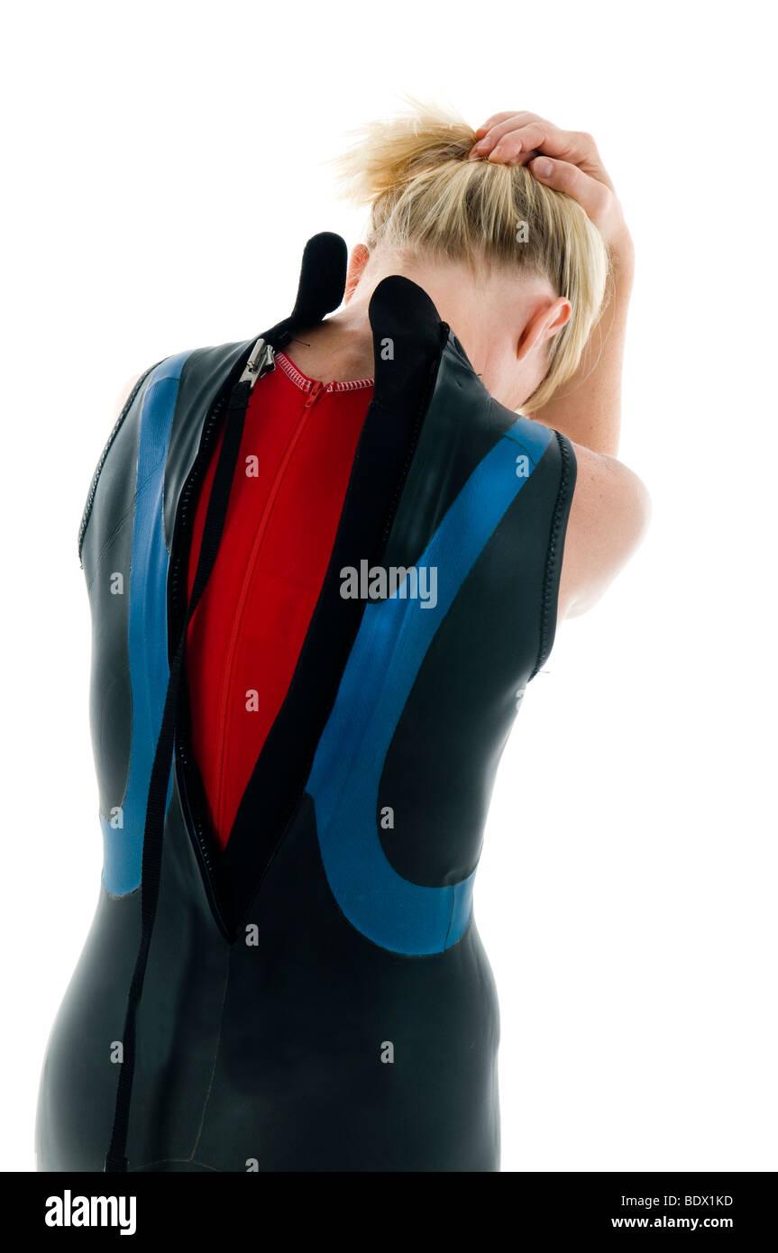 attractive middle age female tri-athlete in marathon wet suit and tight swim suit - Stock Image