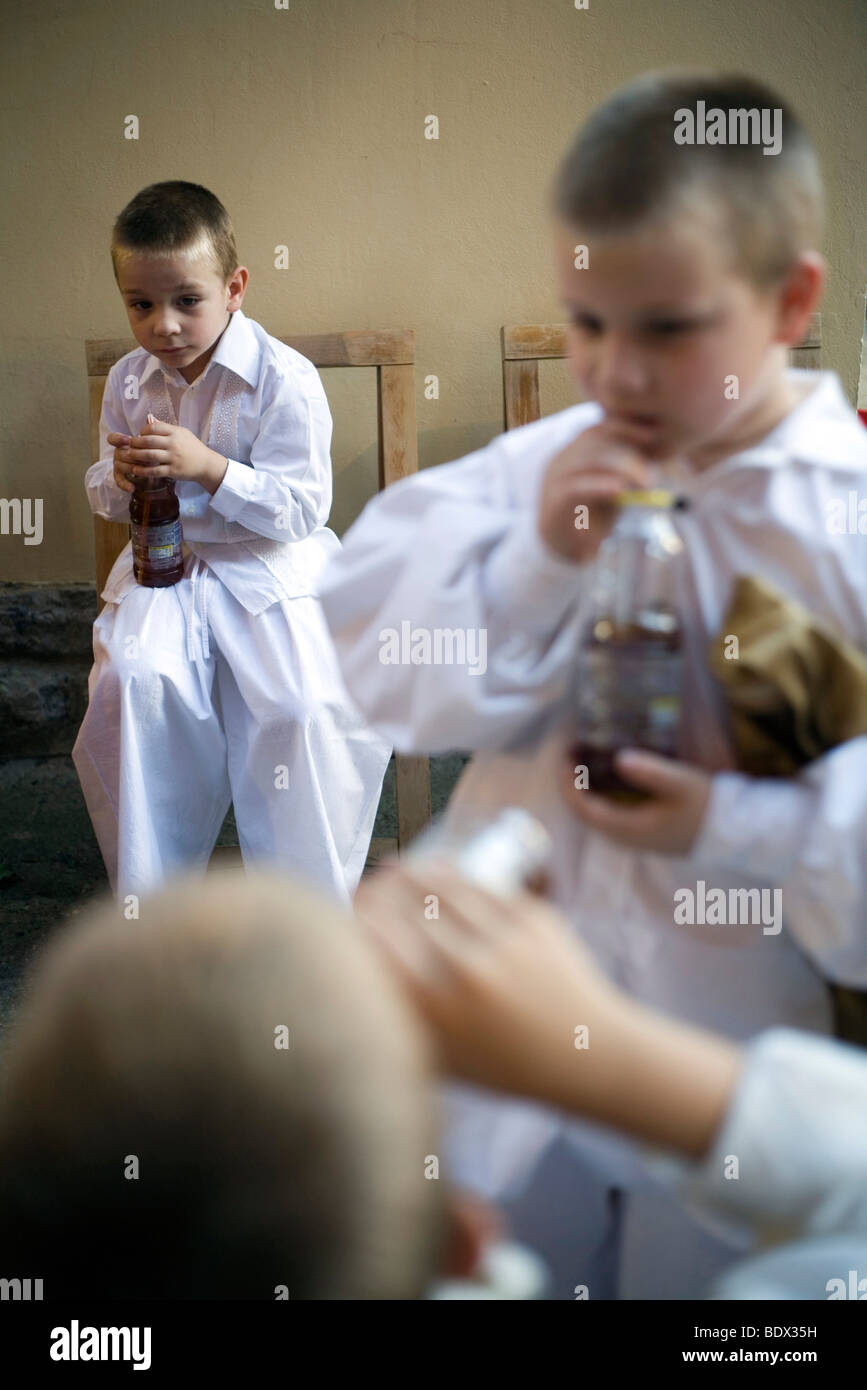 Boys backstage in traditional costume drink soda from bottles during a folk event in Pecs, Hungary - Stock Image
