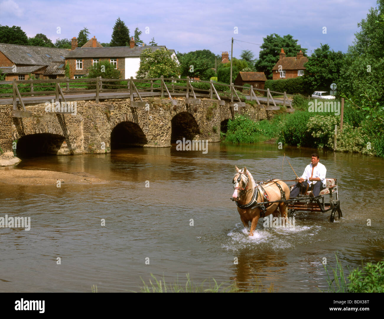 England Surrey Tilford Old bridge with horse & cart crossing river - Stock Image