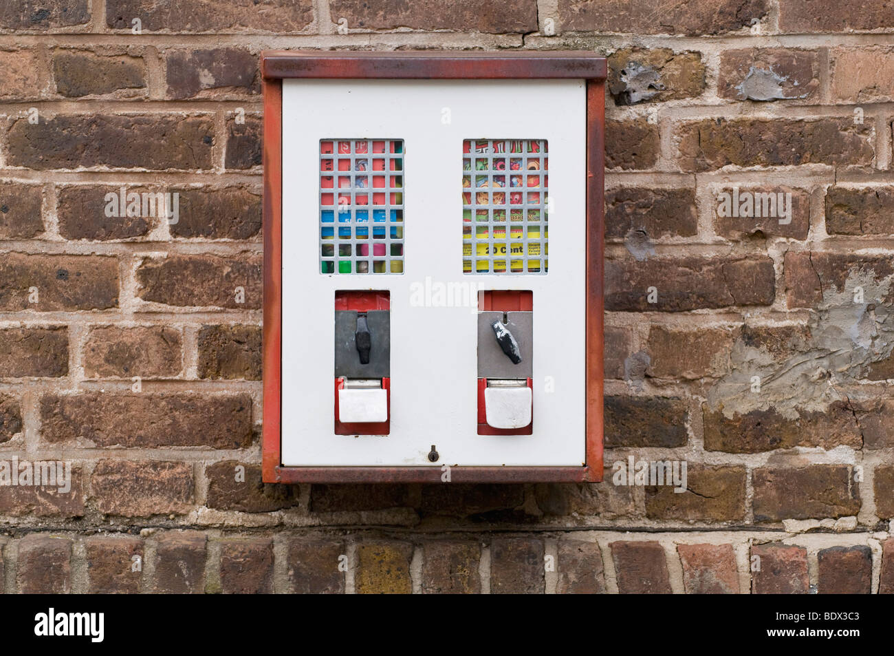 Toy machine and gumball machine on an old brick wall - Stock Image