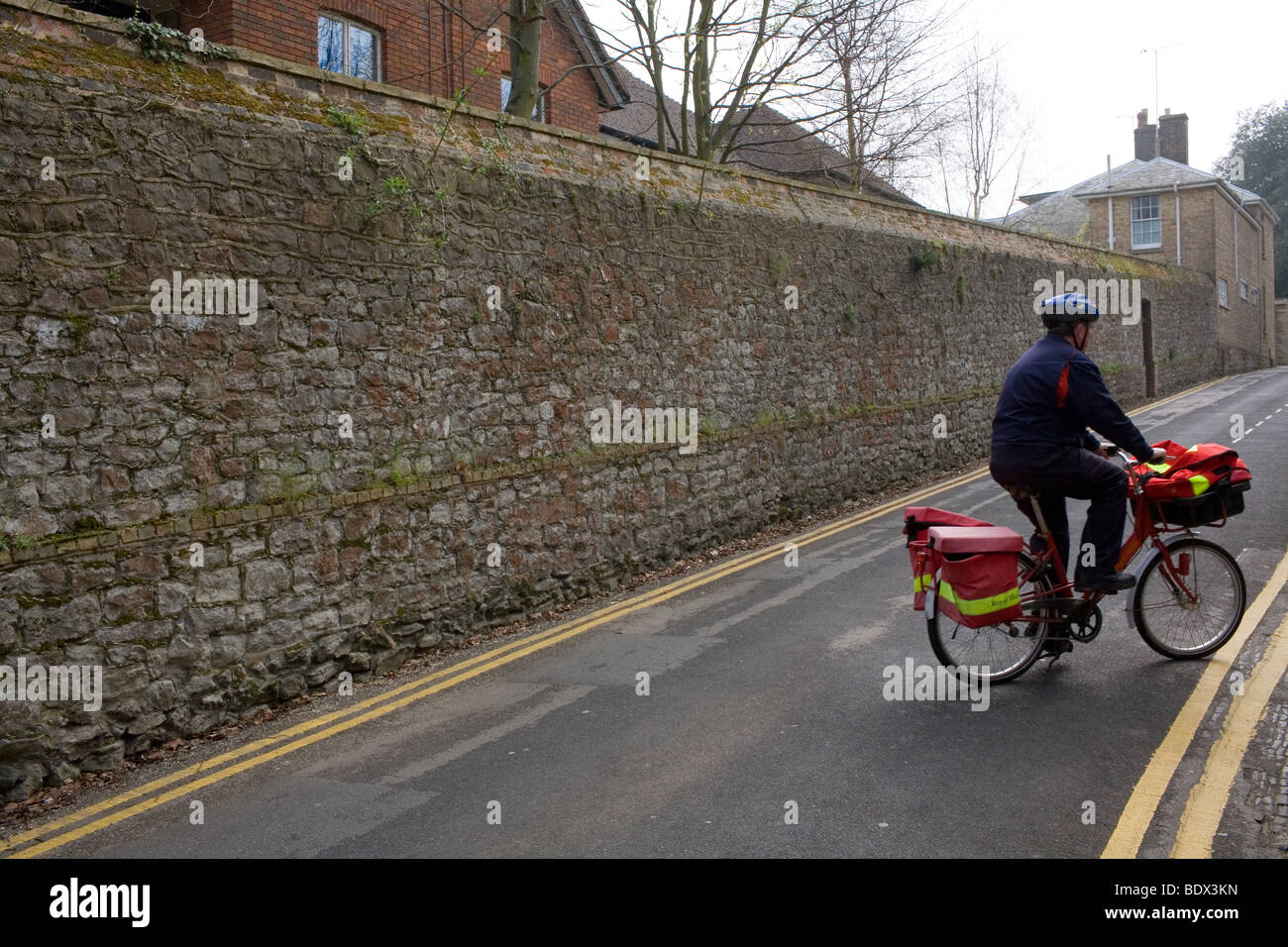 A postman wearing a helmet on a bicycle rides up a country lane to deliver the mail. - Stock Image