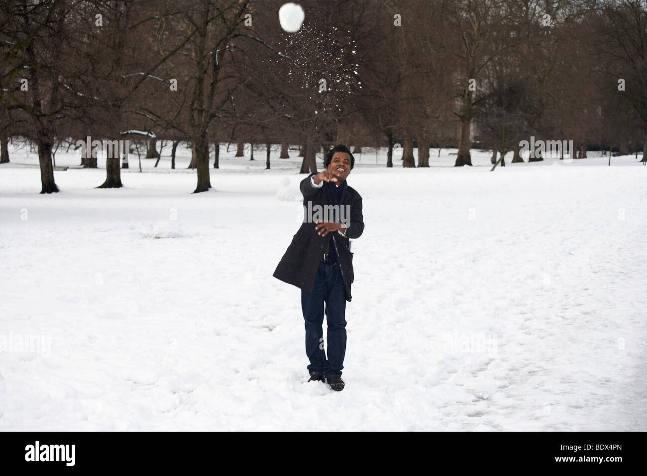 LONDON: MAN THROWING SNOWBALL IN GREEN PARK - Stock Image
