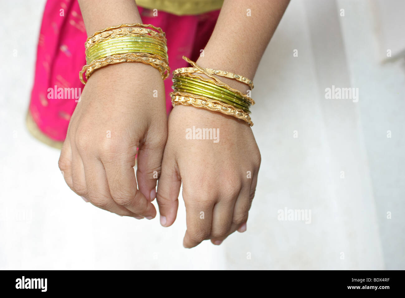 An indian child showing off her fancy bangles in white background - Stock Image