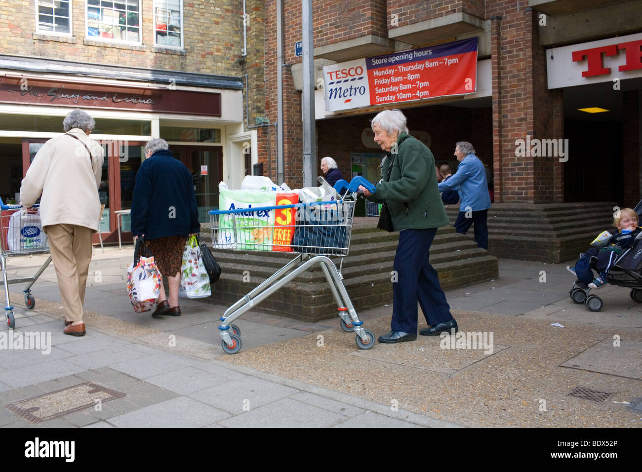 An old woman pushes a trolley full of shopping from Tesco supermarket including a value pack of toilet roll. - Stock Image