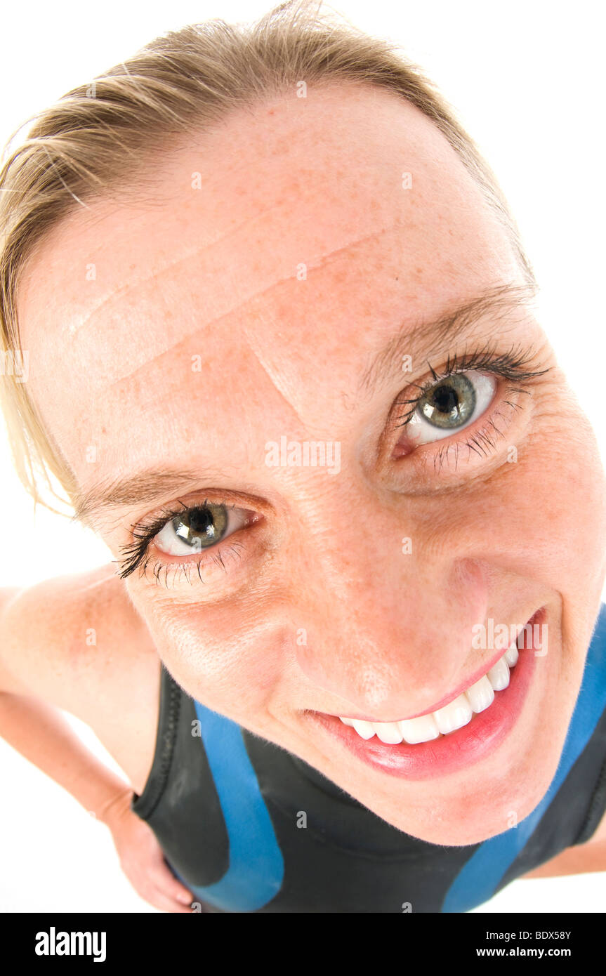 attractive middle age female tri-athlete in marathon wet suit with large head distorted with fish-eye camera lens - Stock Image