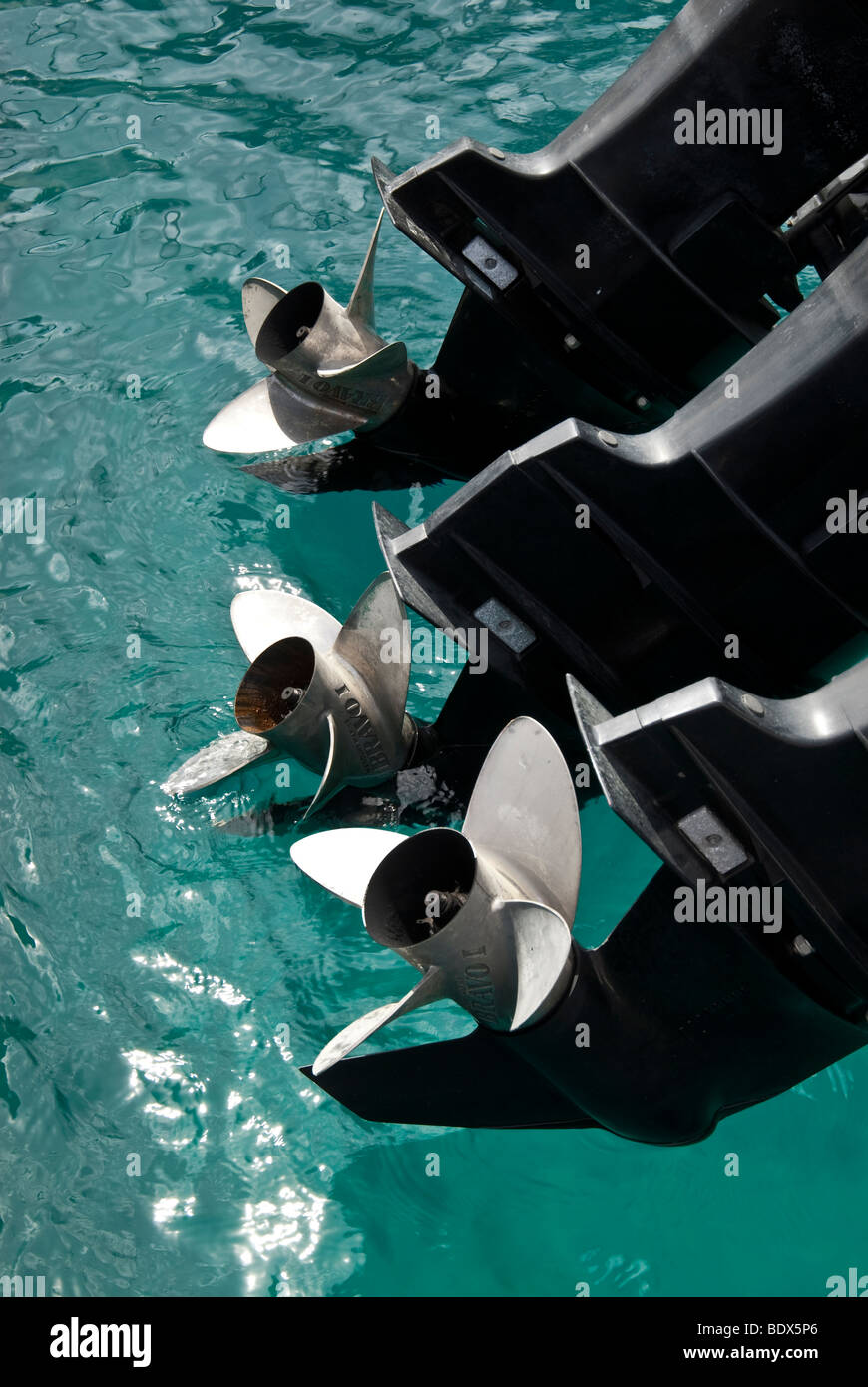 The propellers of a motor boat's outboard motor held out of the water - Stock Image