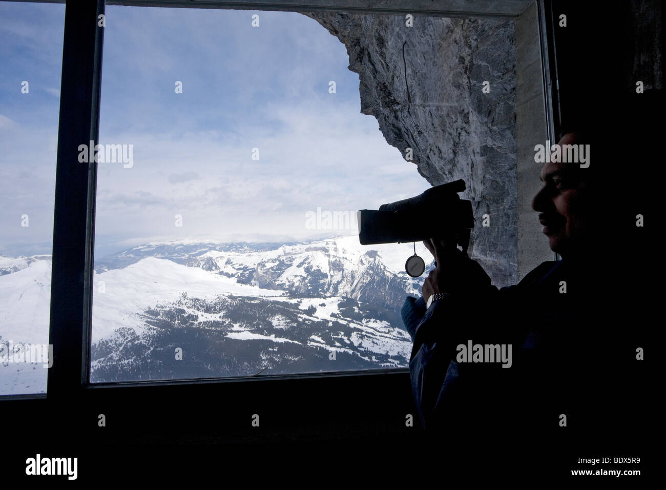 Visitor videos the mountains from viewpoint along the train route from Kleine Scheidegg to Jungfraujoch in Switzerland - Stock Image