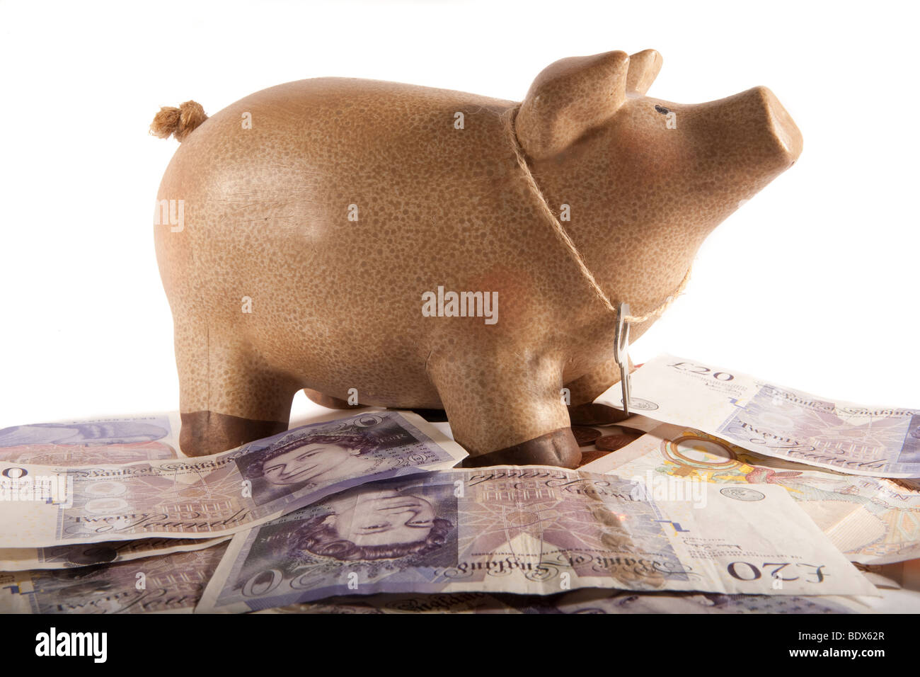 Piggy bank money box with key standing on top of a pile of £20 notes Stock Photo