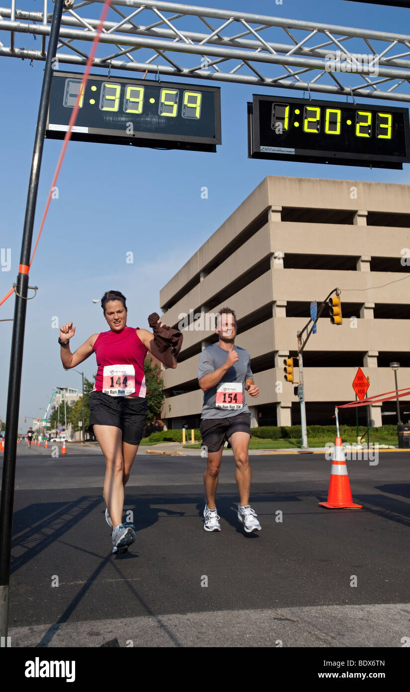 Runners Cross Finish Line in Road Race - Stock Image