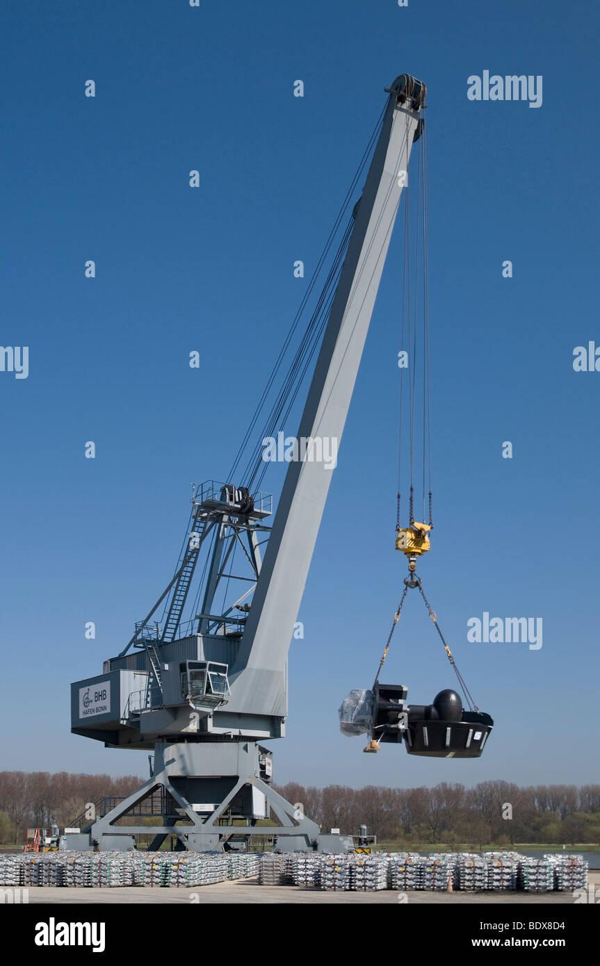 Bonn harbor, crane loading parts of a turbine engine, in front aluminum ingots ready for pick-up, Bonn, North Rhine - Stock Image