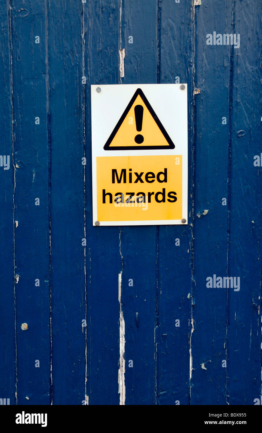 A blue wooden door with a warning sign of 'mixed hazards'. - Stock Image