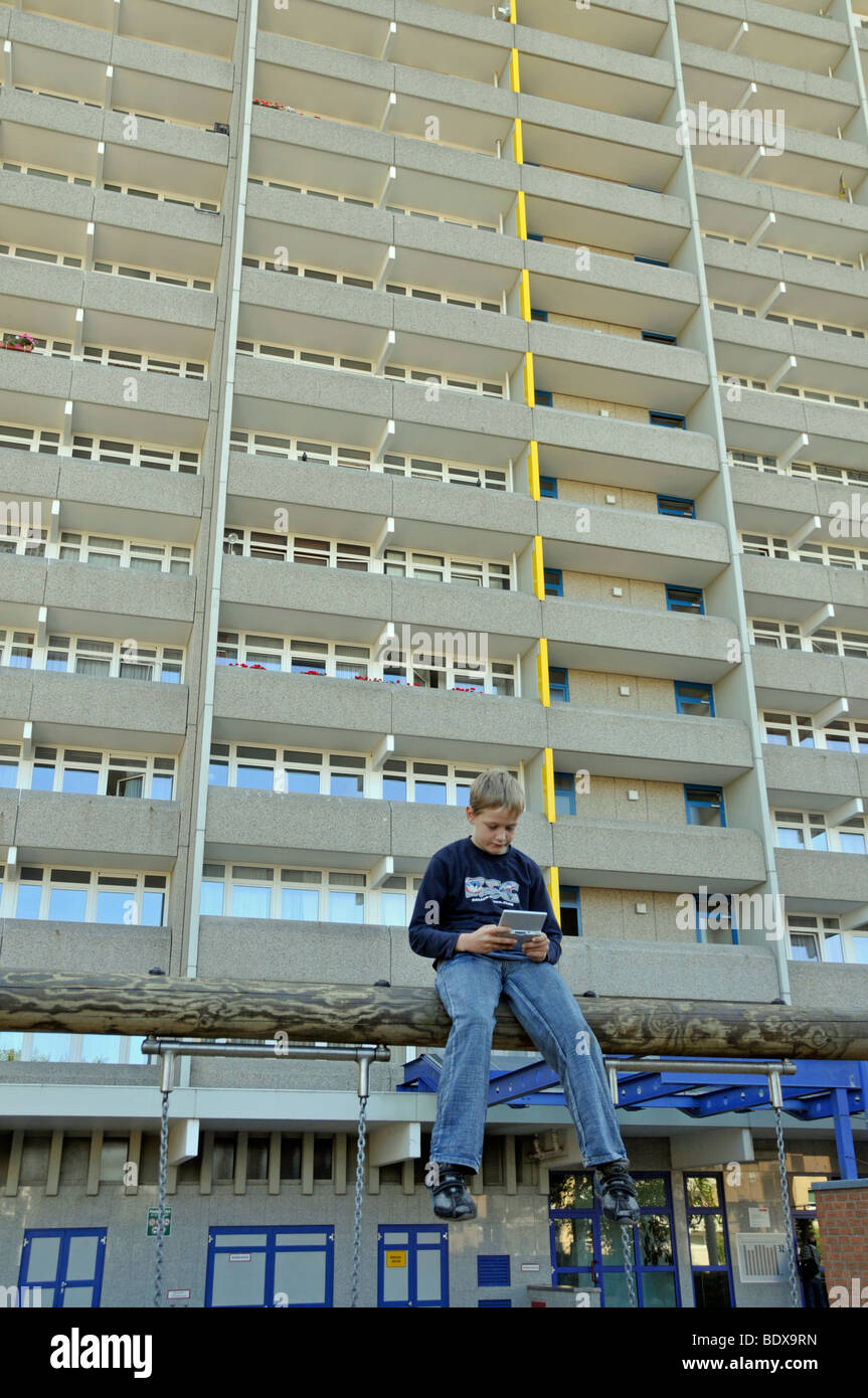 Boy 9 Playing With His Nintendo In Front Of A High Rise