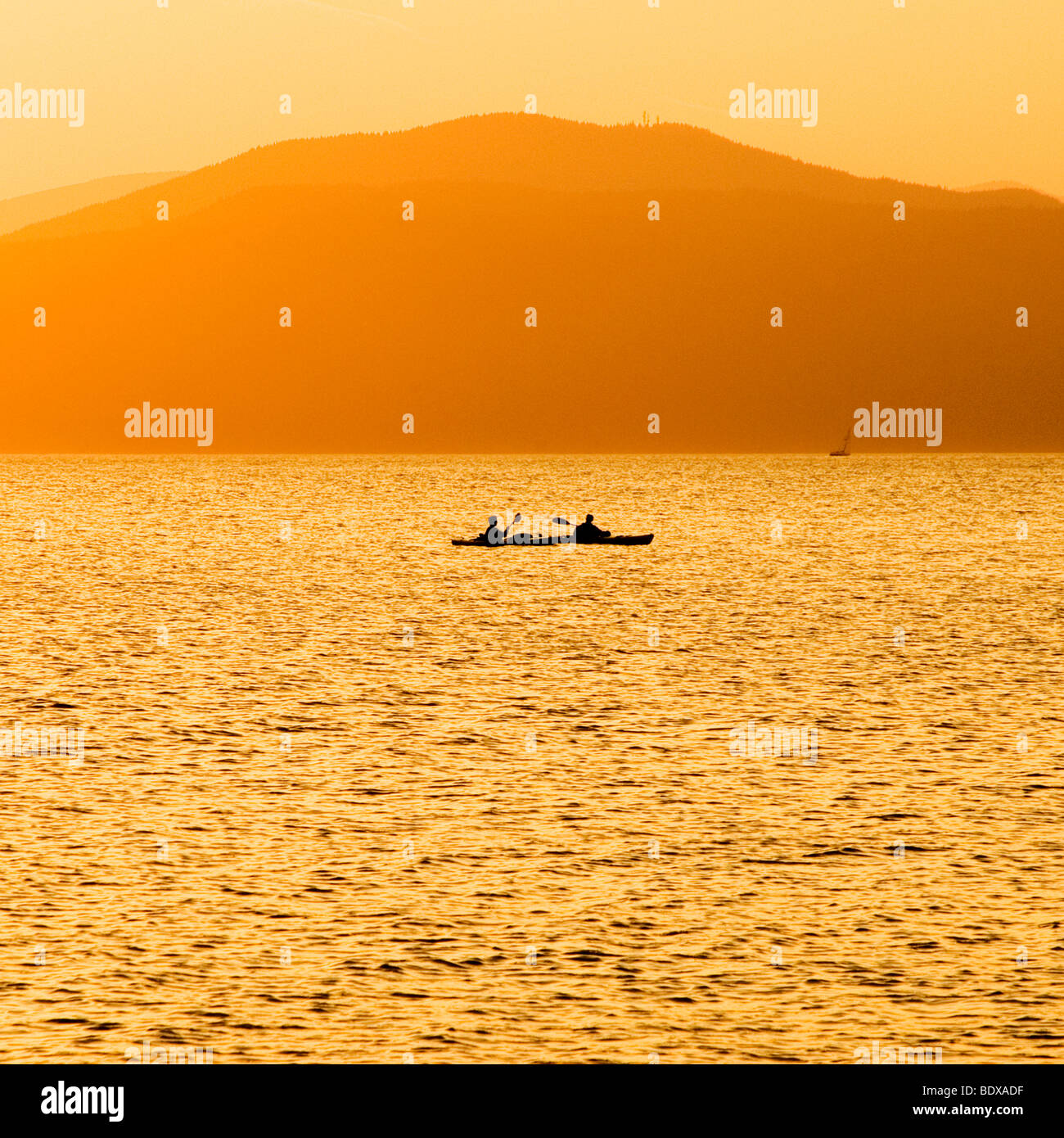 Sunset with silhouette of people kayaking on ocean, mountains in background, Jericho Beach, Vancouver - Stock Image