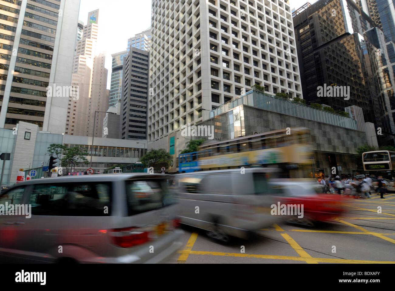 Dense traffic in the narrow streets of Hong Kong between skyscrapers, in Central, Hong Kong, China, Asia - Stock Image