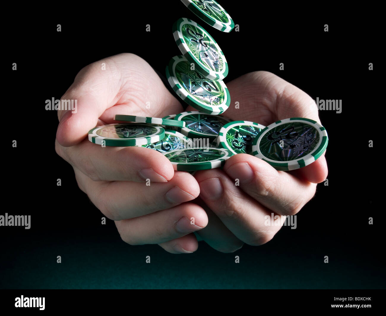 Several green twenty five valued chips falling on a pair of hands isolated over a black background. - Stock Image