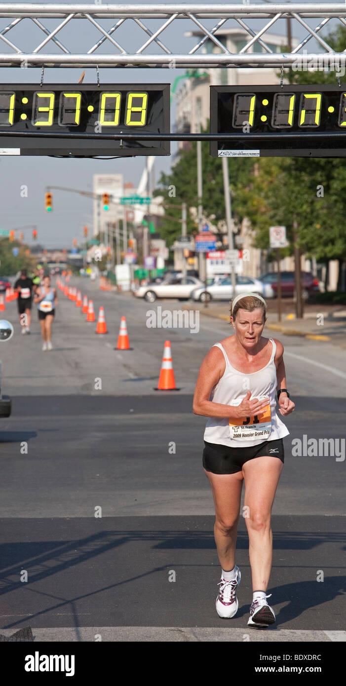 Runner Crosses Finish Line in Road Race - Stock Image