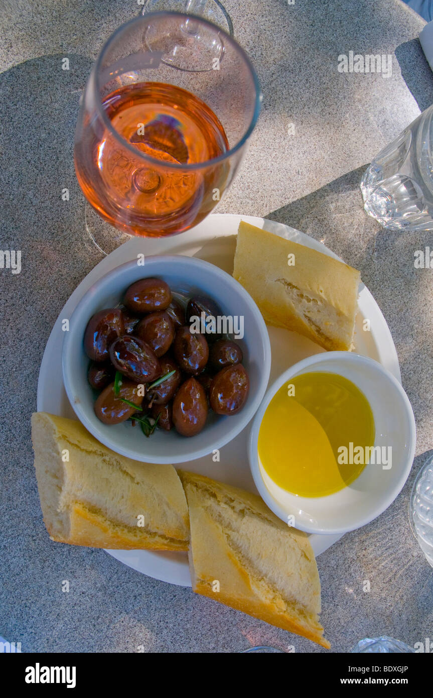 An appetiser of organically grown olives, olive oil and crisp bread with a glass of rose - Stock Image