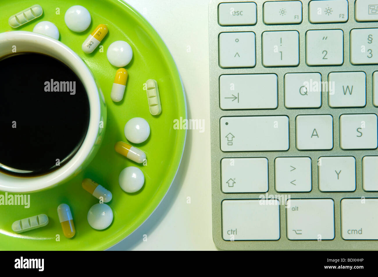 Uppers and psychotropic drugs next to a computer keyboard, symbolic image for doping at work Stock Photo