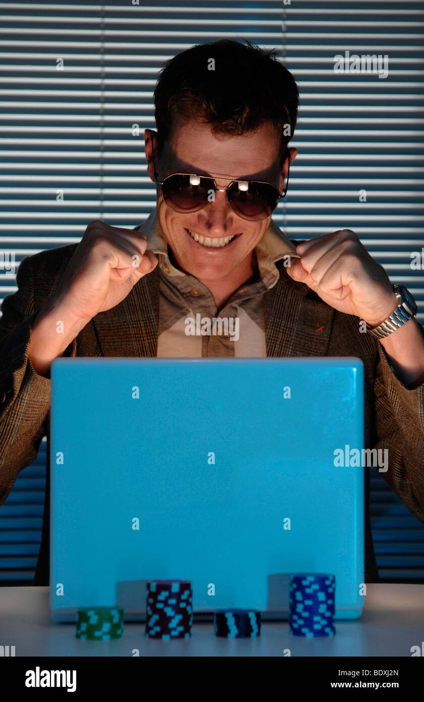 Man playing online poker on the laptop Stock Photo