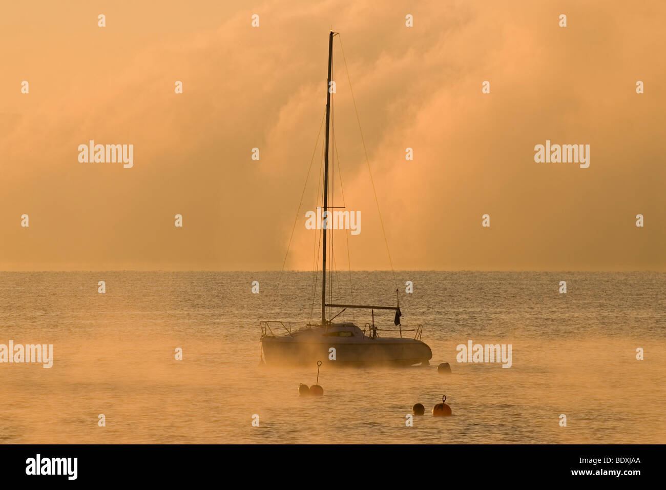 Sailing boat and low morning fog over Ammersee lake at Utting, Bavaria, Germany, Europe Stock Photo