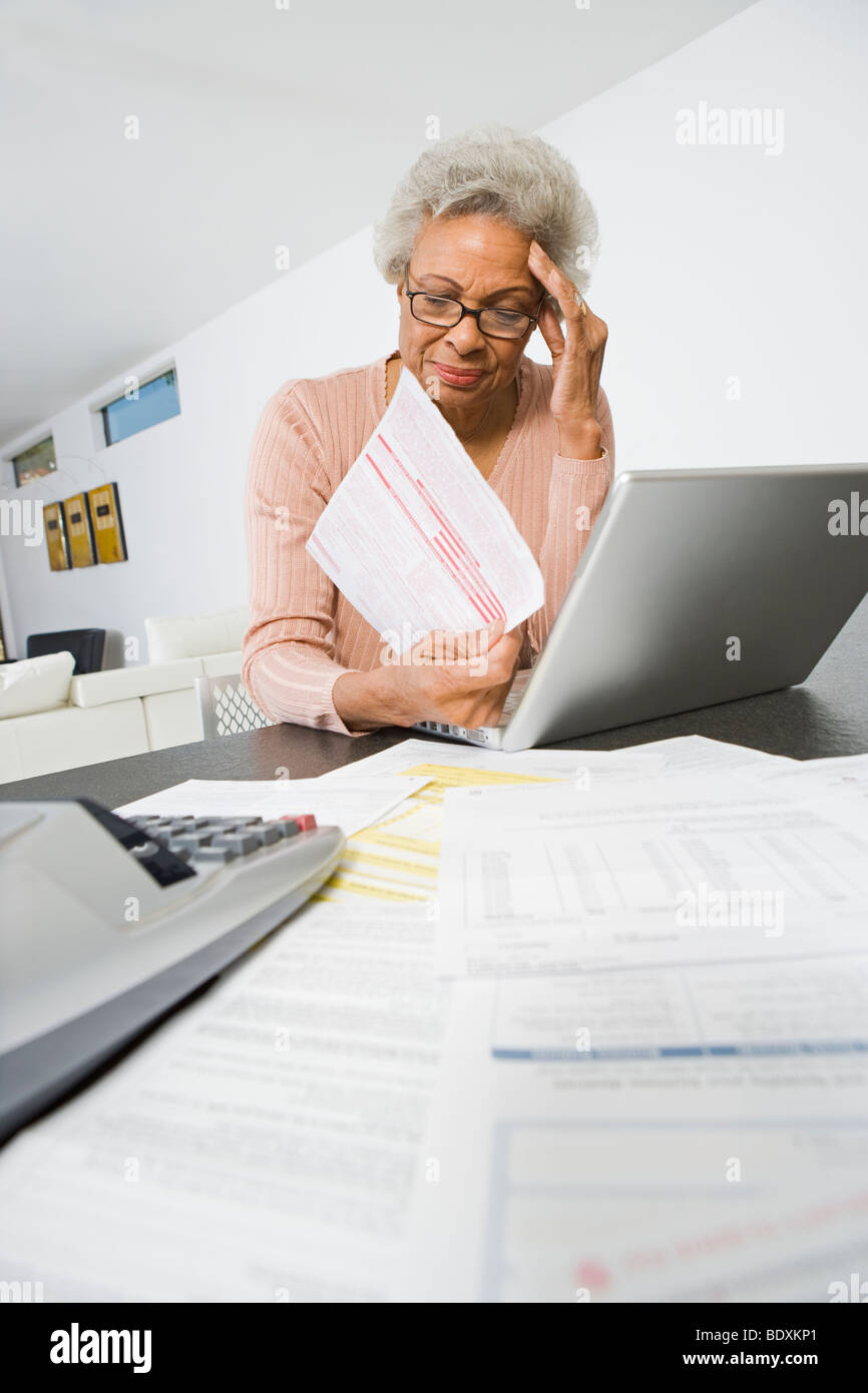Senior Woman Worrying About Home Finances - Stock Image