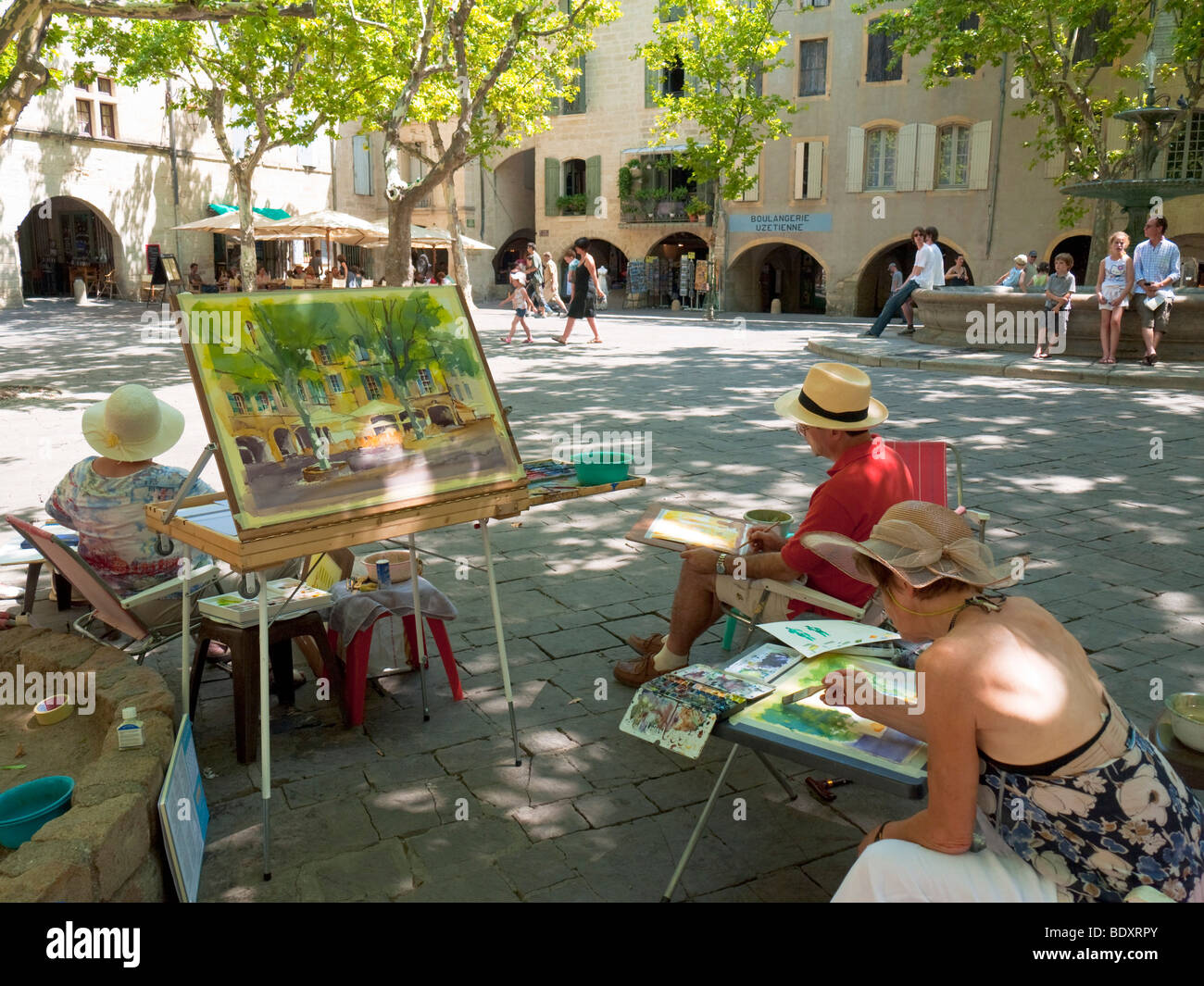 Hobby painters work on the central square Place aux Herbes at Uzès, southern France. - Stock Image