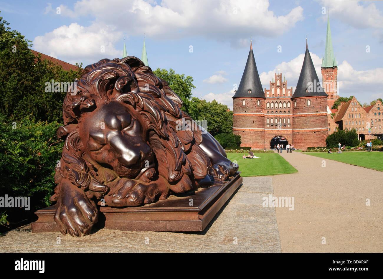 Sculpture Sleeping Lion in front of the Holstentor, Holsten Gate, in Luebeck, Schlewig-Holstein, Germany, Europe - Stock Image