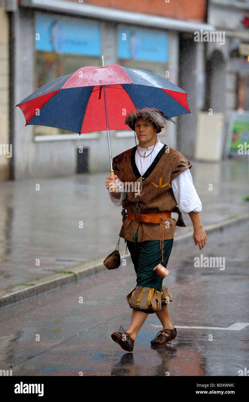 Historically dressed man with umbrella - Stock Image