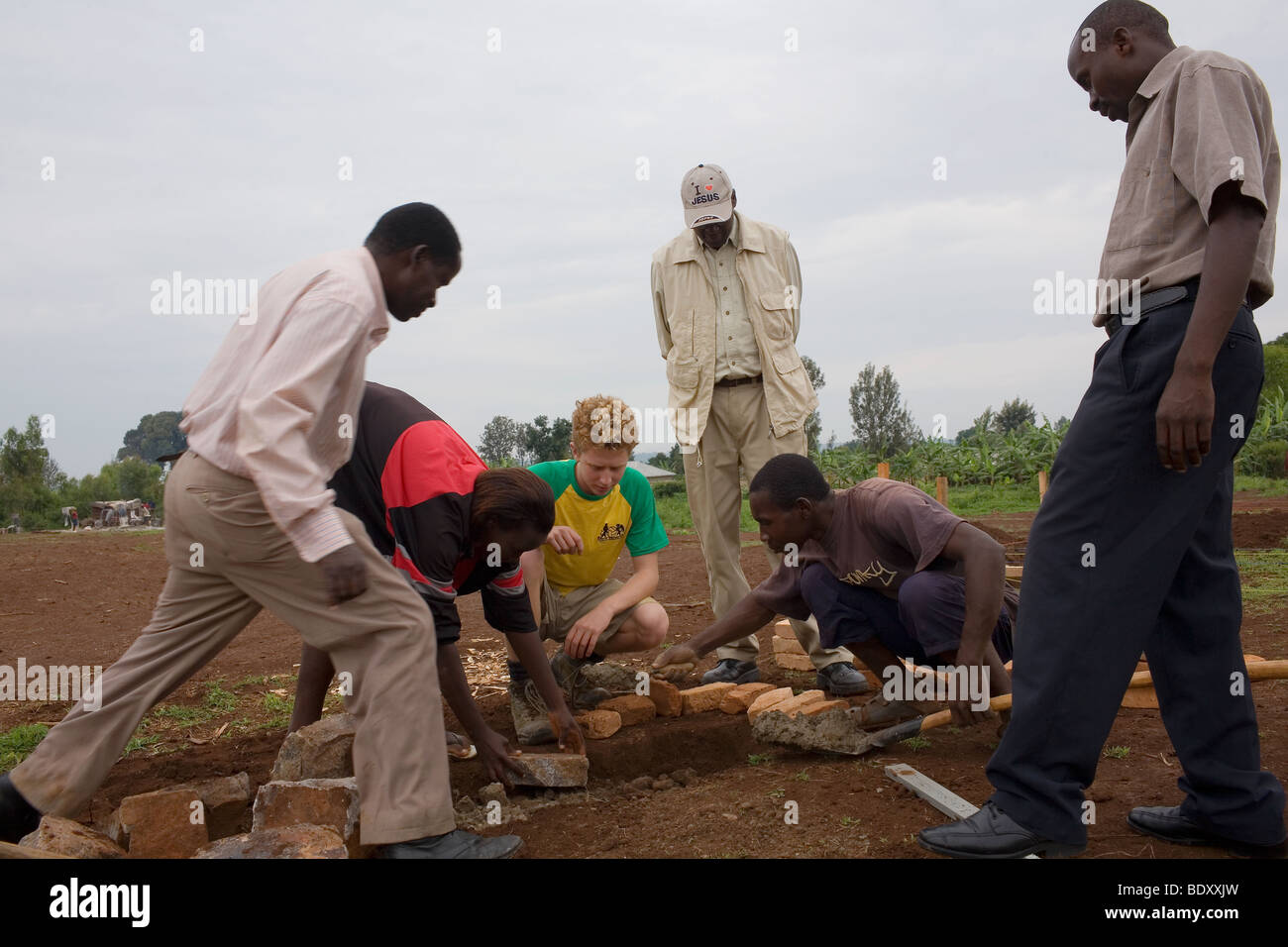 A white skinned red haired public schoolboy volunteers for a building project in a Rwandan village. - Stock Image