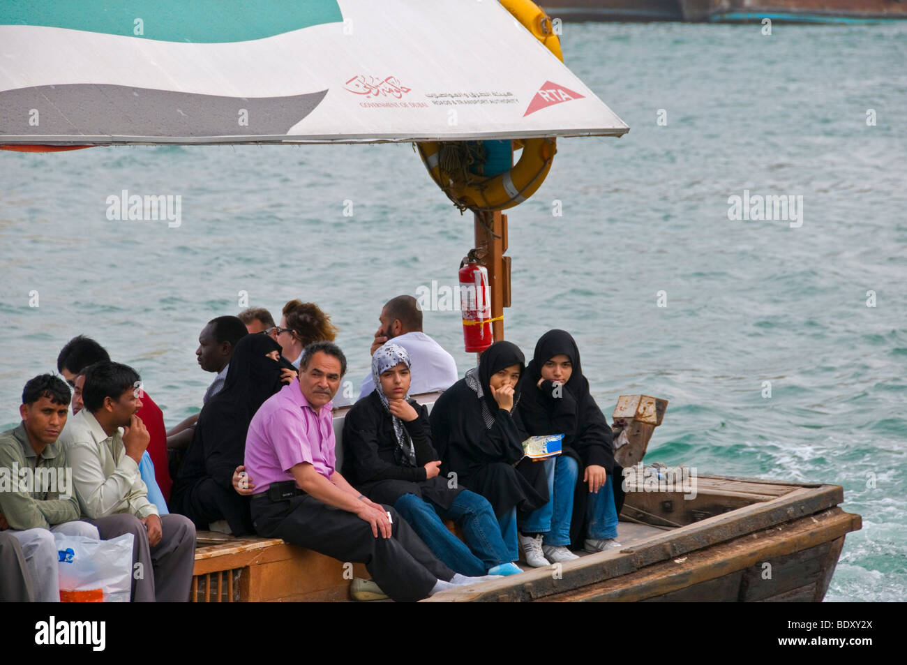Passengers in Dhow boats in the Dubai creek - Stock Image